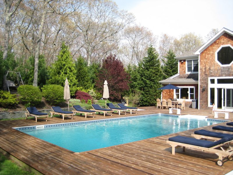 Pristine saltwater pool & deck with poolside dining and entertainment areas at HamptonsGetaway, a Hamptons rental.