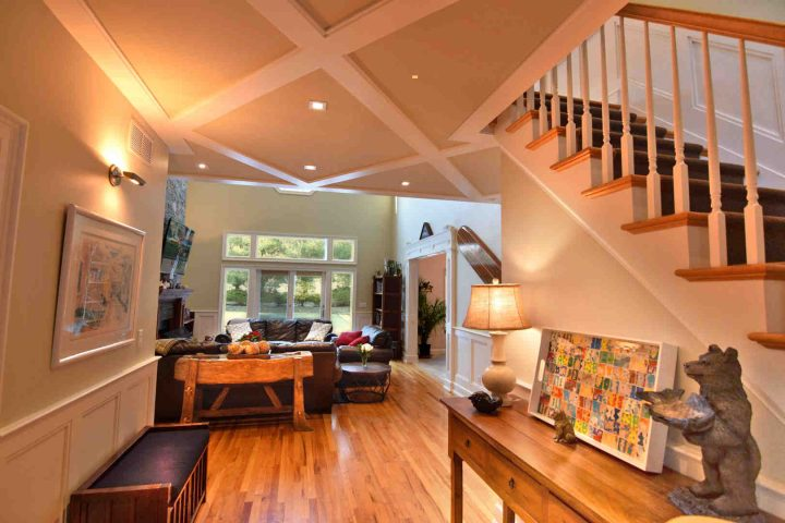 View of wainscoted entrance hall and open staircase looking into great room of HamptonsGetaway, a Hamptons rental.