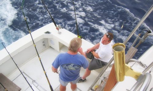 Men talking and fishing on a boat on the ocean.
