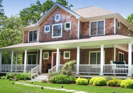 The front view of the HamptonsGetaway; a prime Hamptons rental property. It is a large house with a wrap-around porch and beautiful grounds,