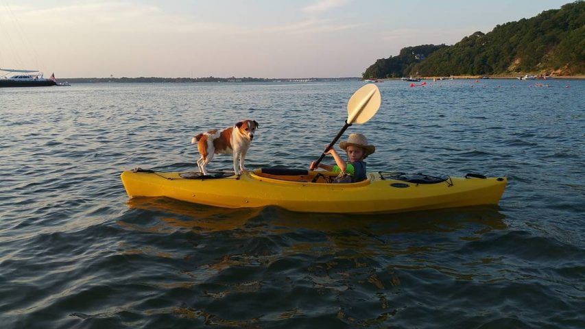 Boy, dog and yellow kayak.
