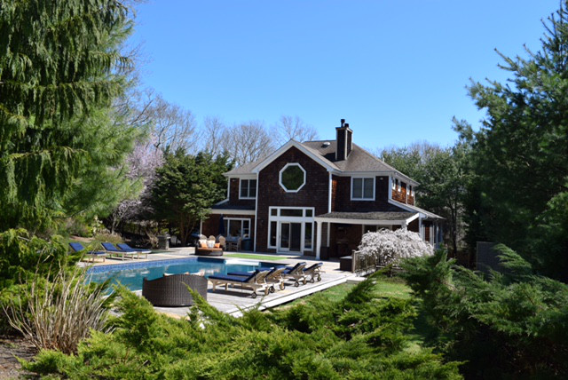 View of landscaped grounds, saltwater pool, spacious deck with lounge chairs all behind the gorgeous Hamptons rental house, HamptonsGetaway.