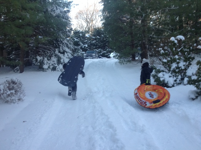 Children sledding on the driveway.